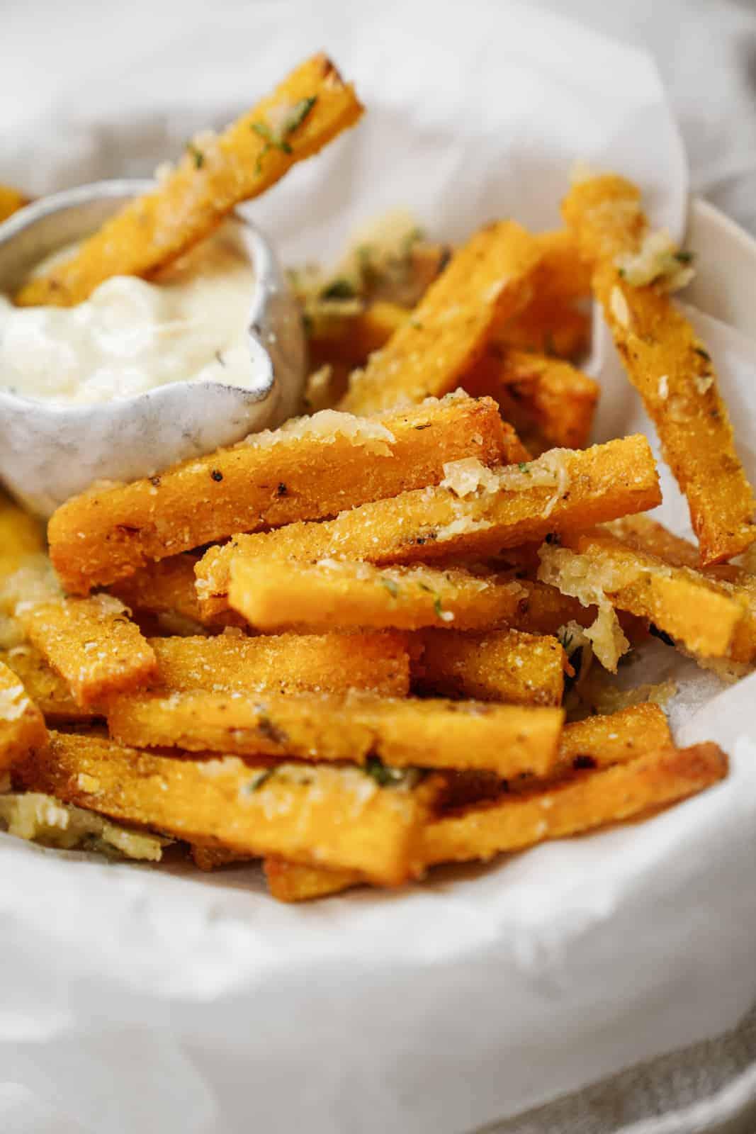 A bowl of vegan polenta fries with a side of vegan aioli