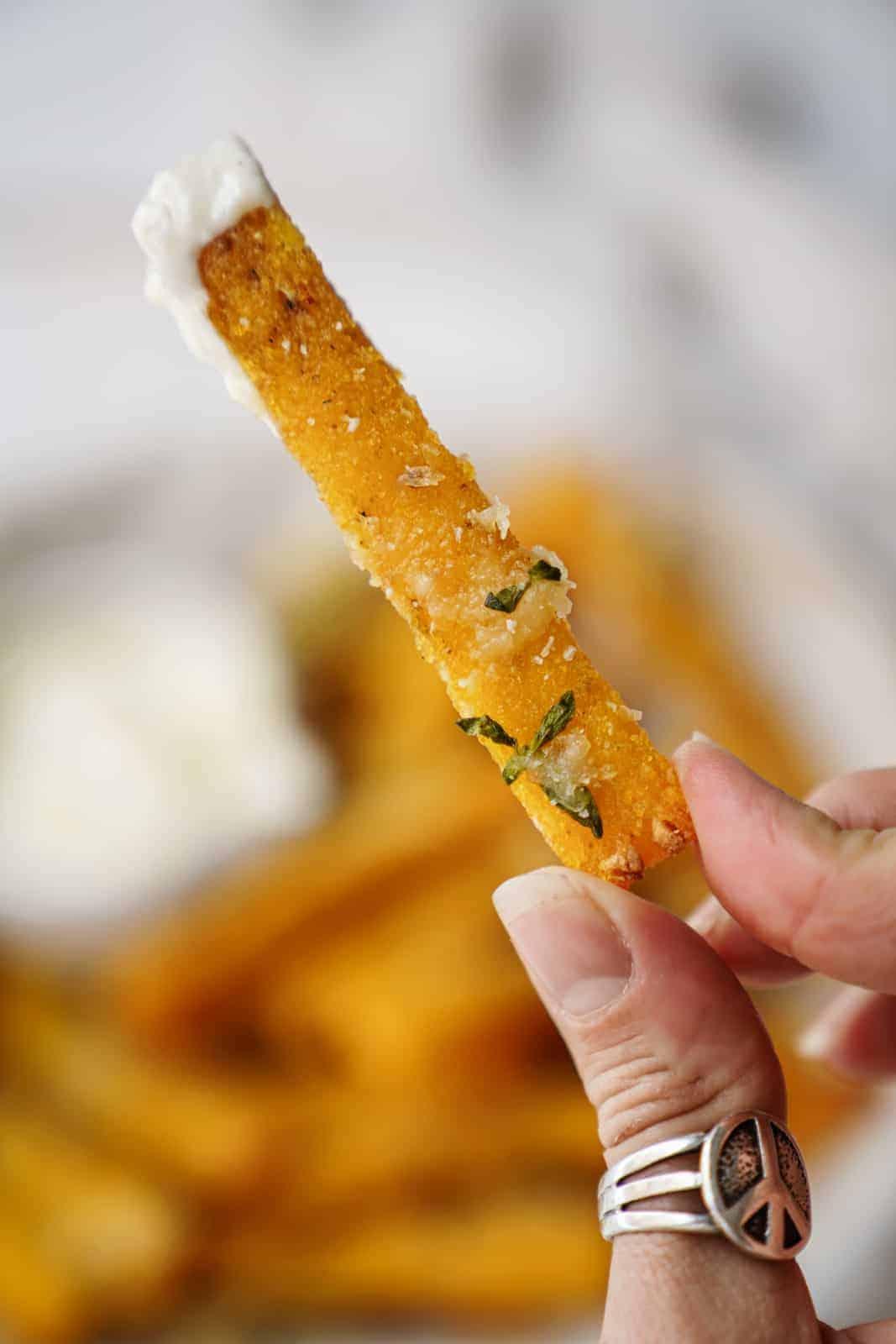 Hand holding a vegan polenta fry dipped in vegan aioli