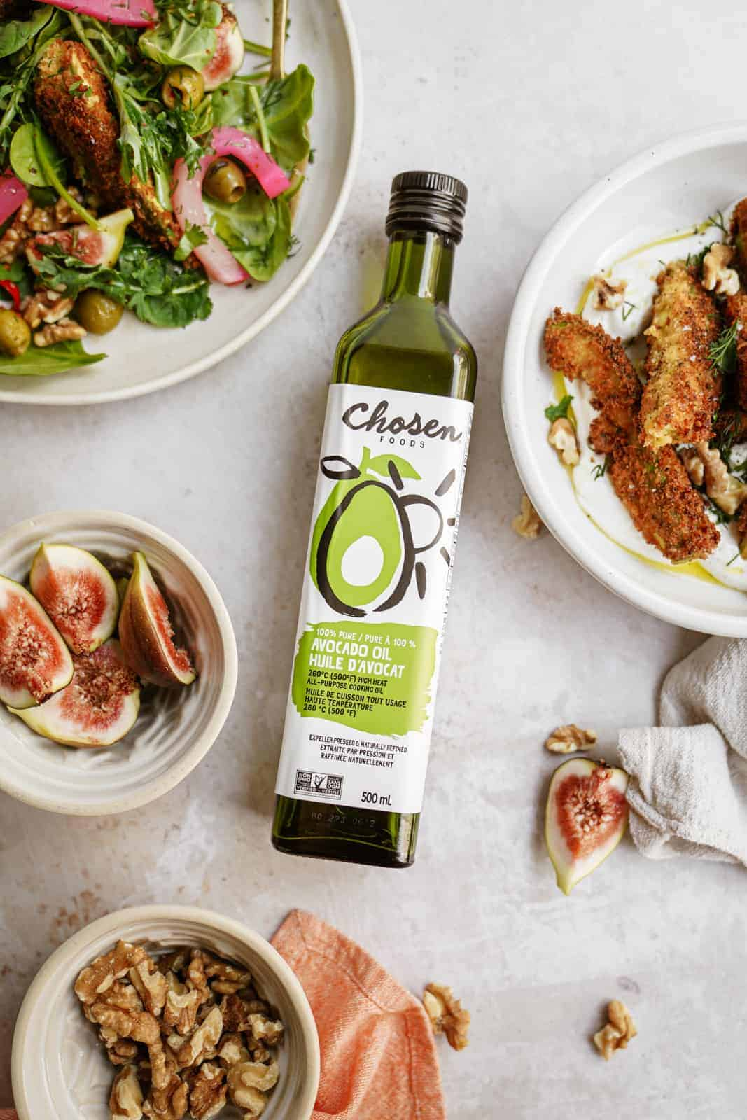 Chosen Foods Avocado Oil on counter surrounded by Avocado Fried Salad on plates
