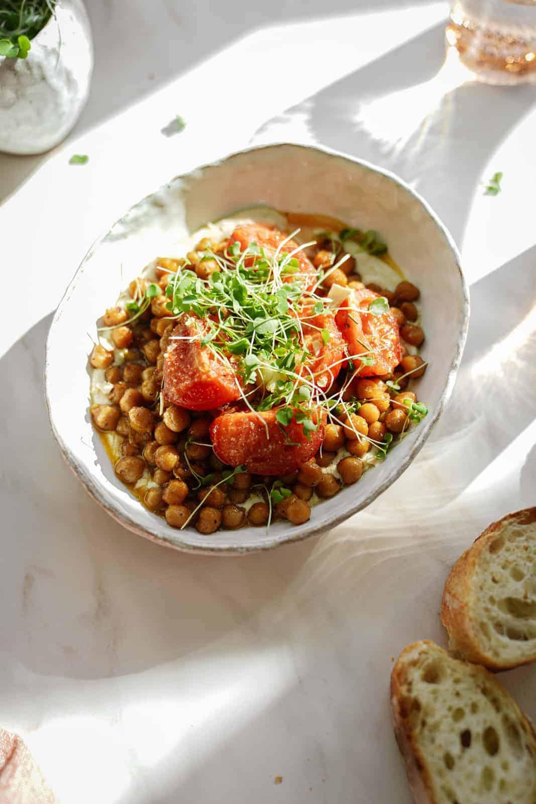 oven-roasted chickpeas in a white bowl with slices of bread next to it