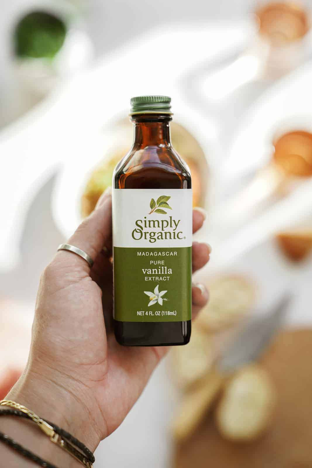 Hand holding a bottle of Simply Organic Vanilla Extract