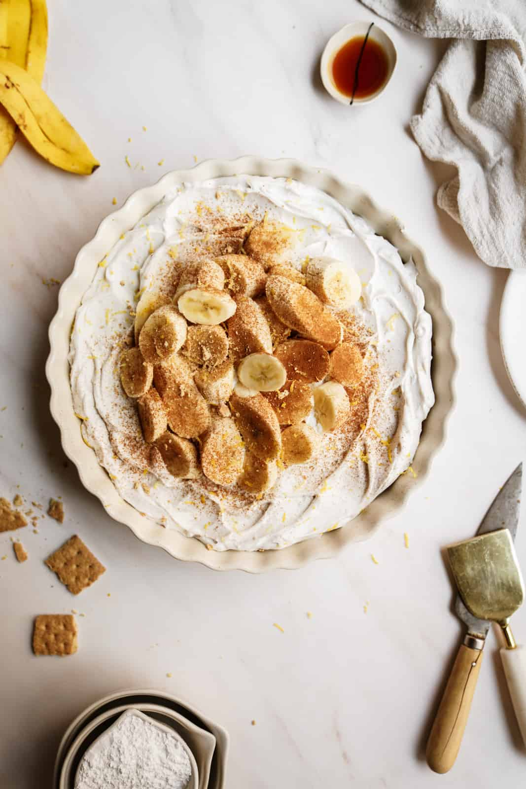 Easy vegan banana cream pie on countertop with fresh bananas on top