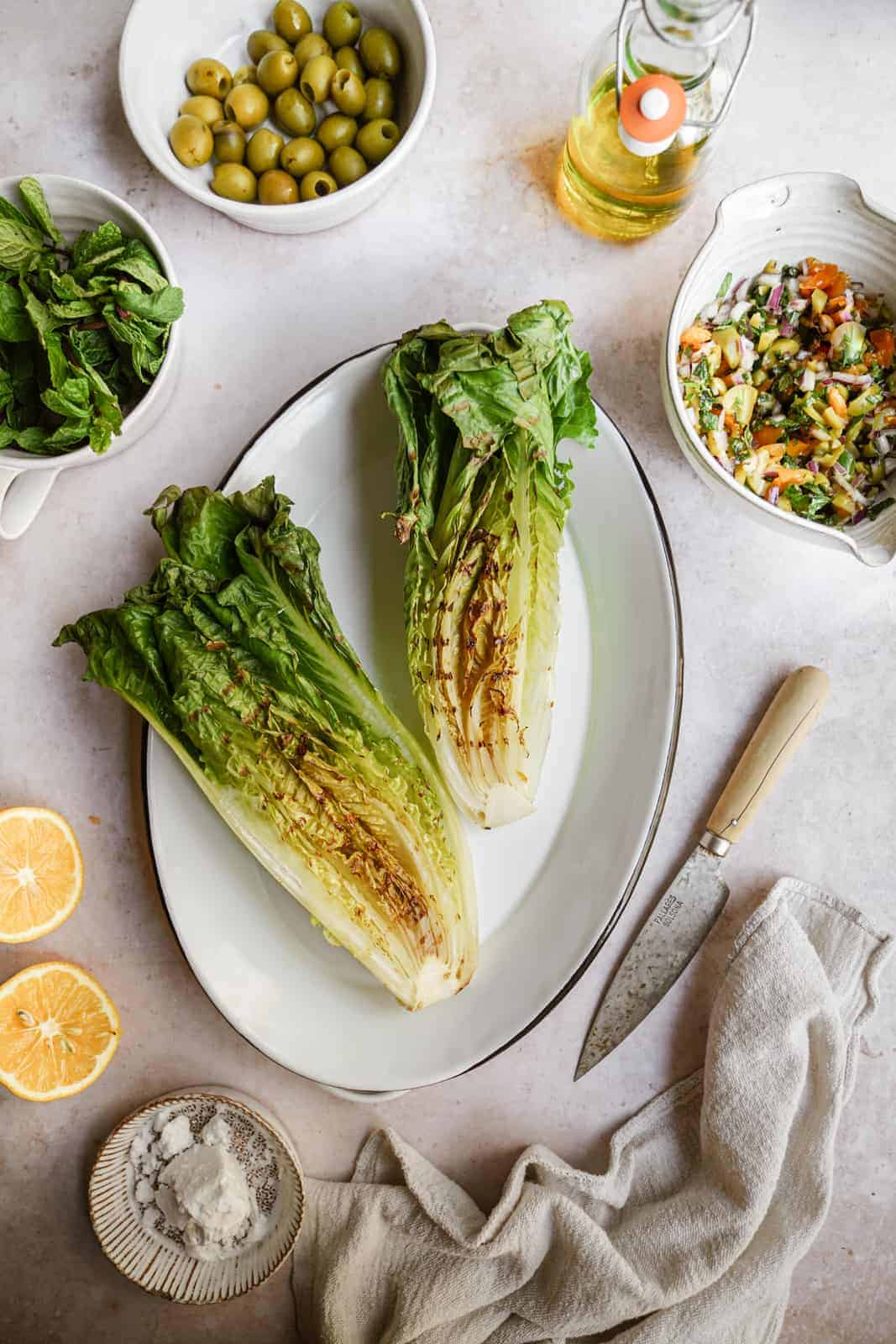 grilled romaine lettuce heads on a serving dish