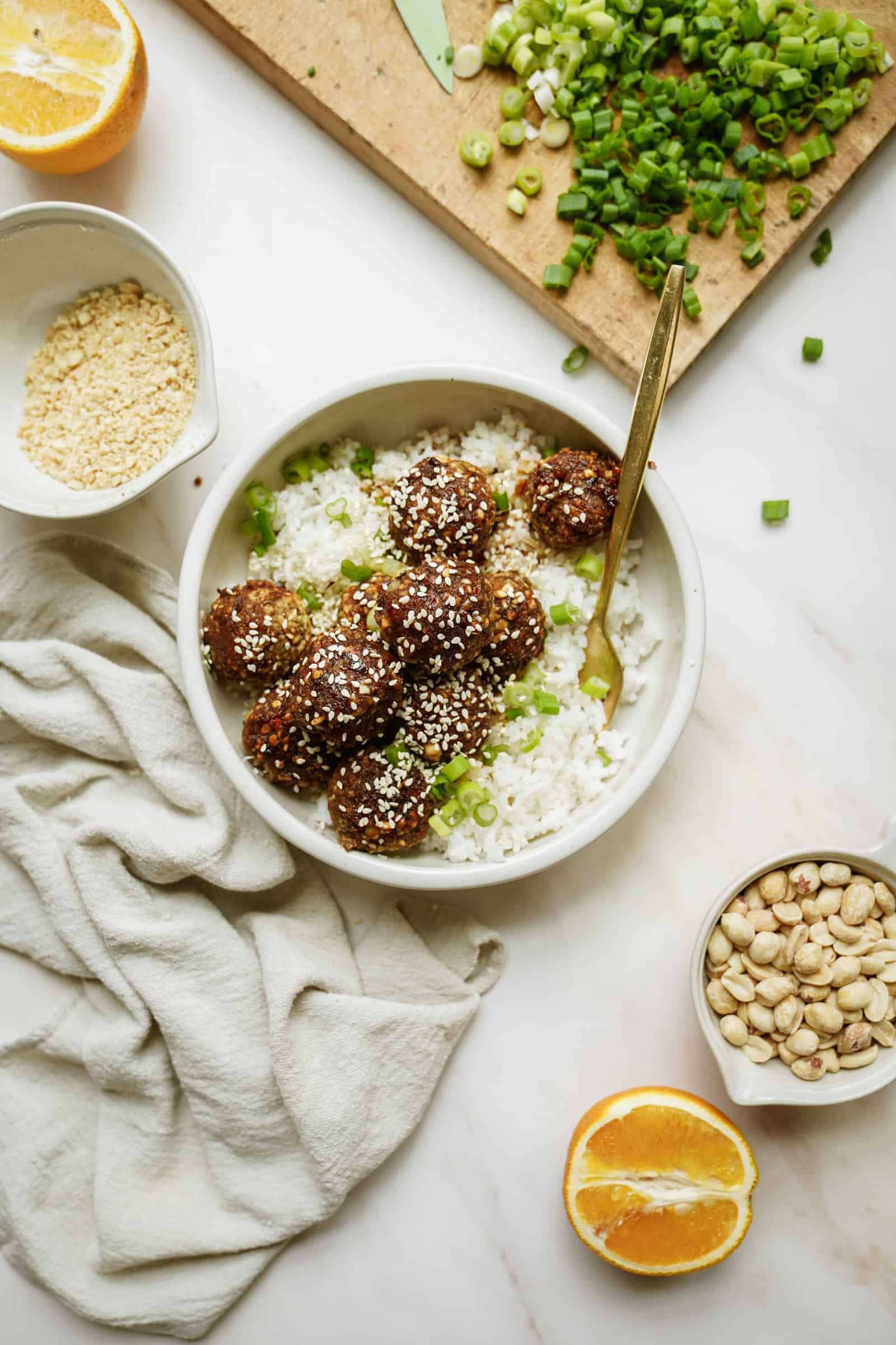 A bowl of lentil meatballs over rice with fresh ingredients