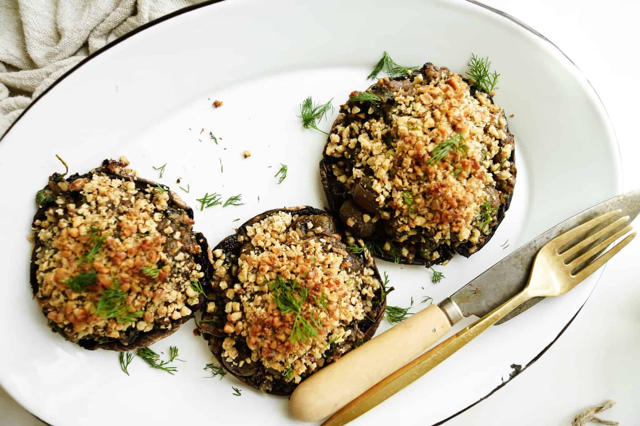 Vegan Stuffed Portobello Mushrooms on a serving plate with a fork and knife