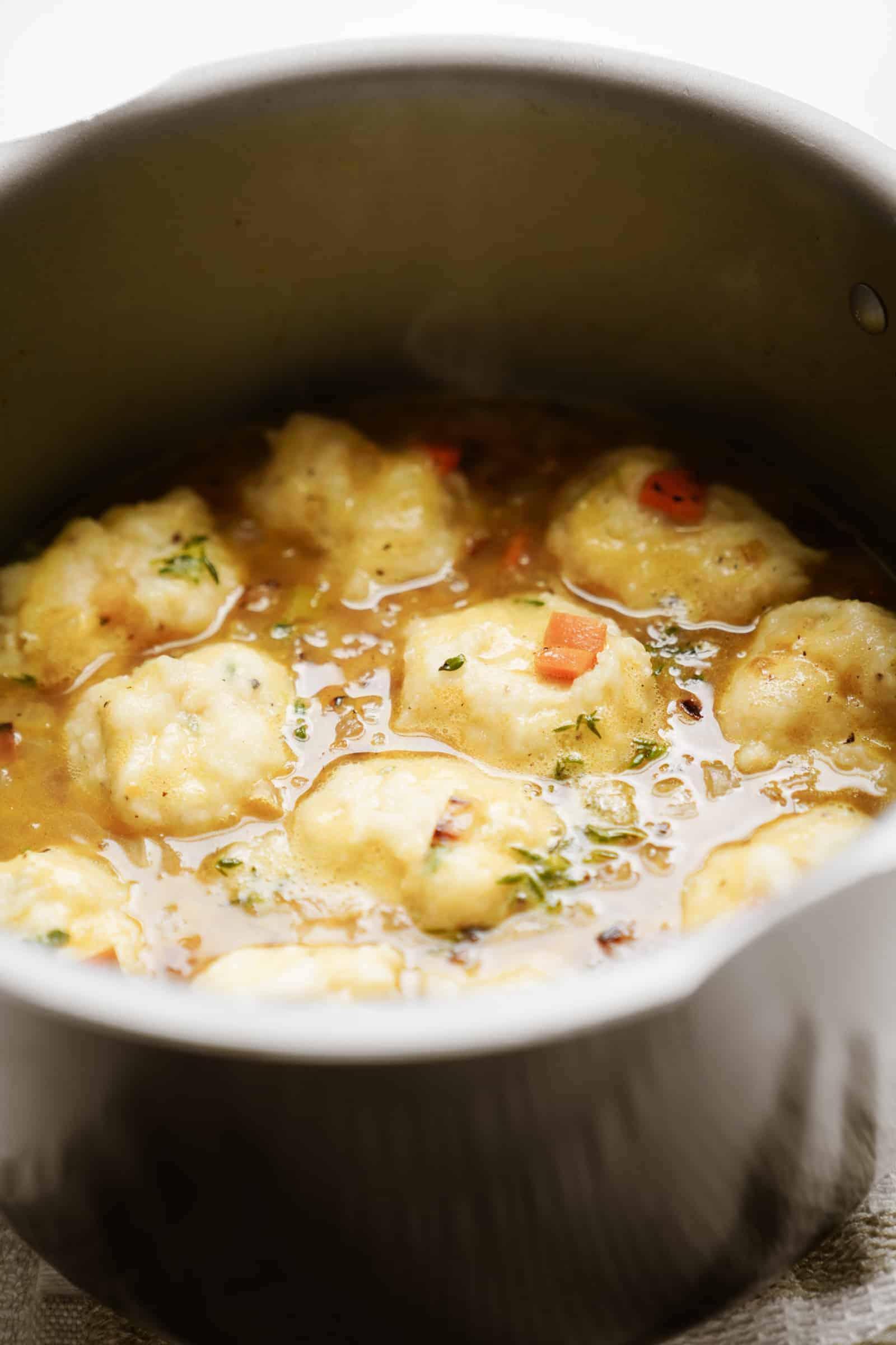 Vegan dumplings in a pot of soup cooking