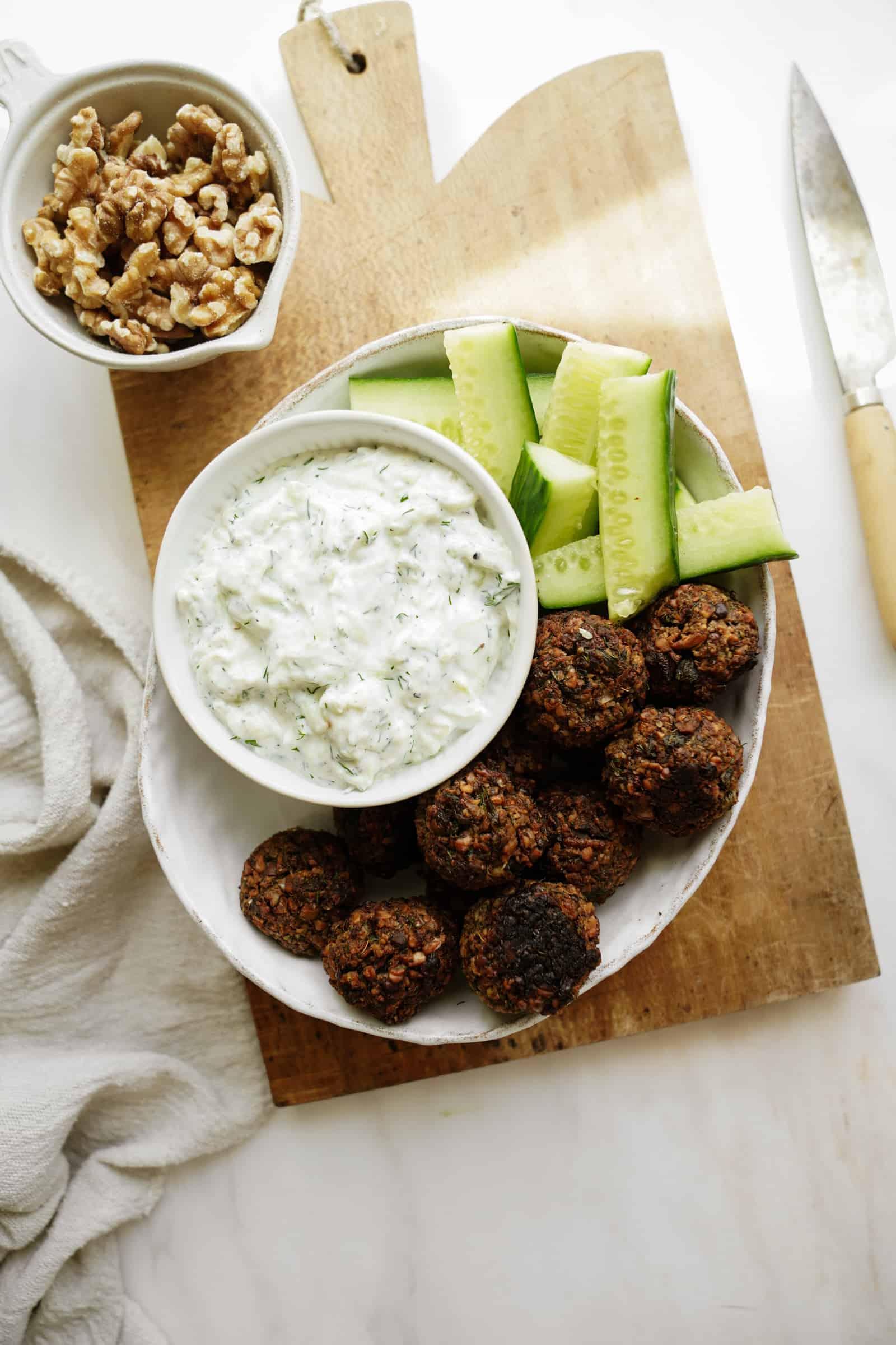 Vegan walnut meatballs on a serving dish with homemade tzaziki
