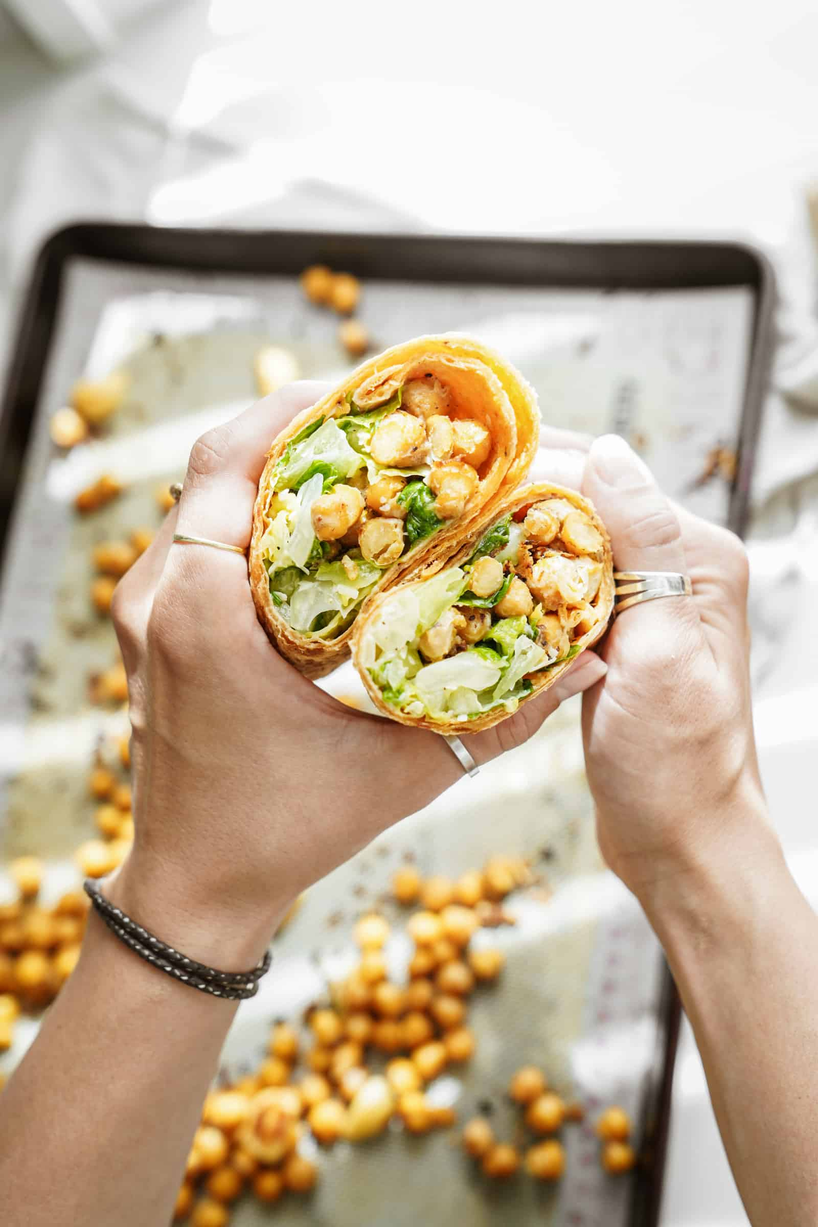 chickpea caesar salad wrap open and being held by 2 hands