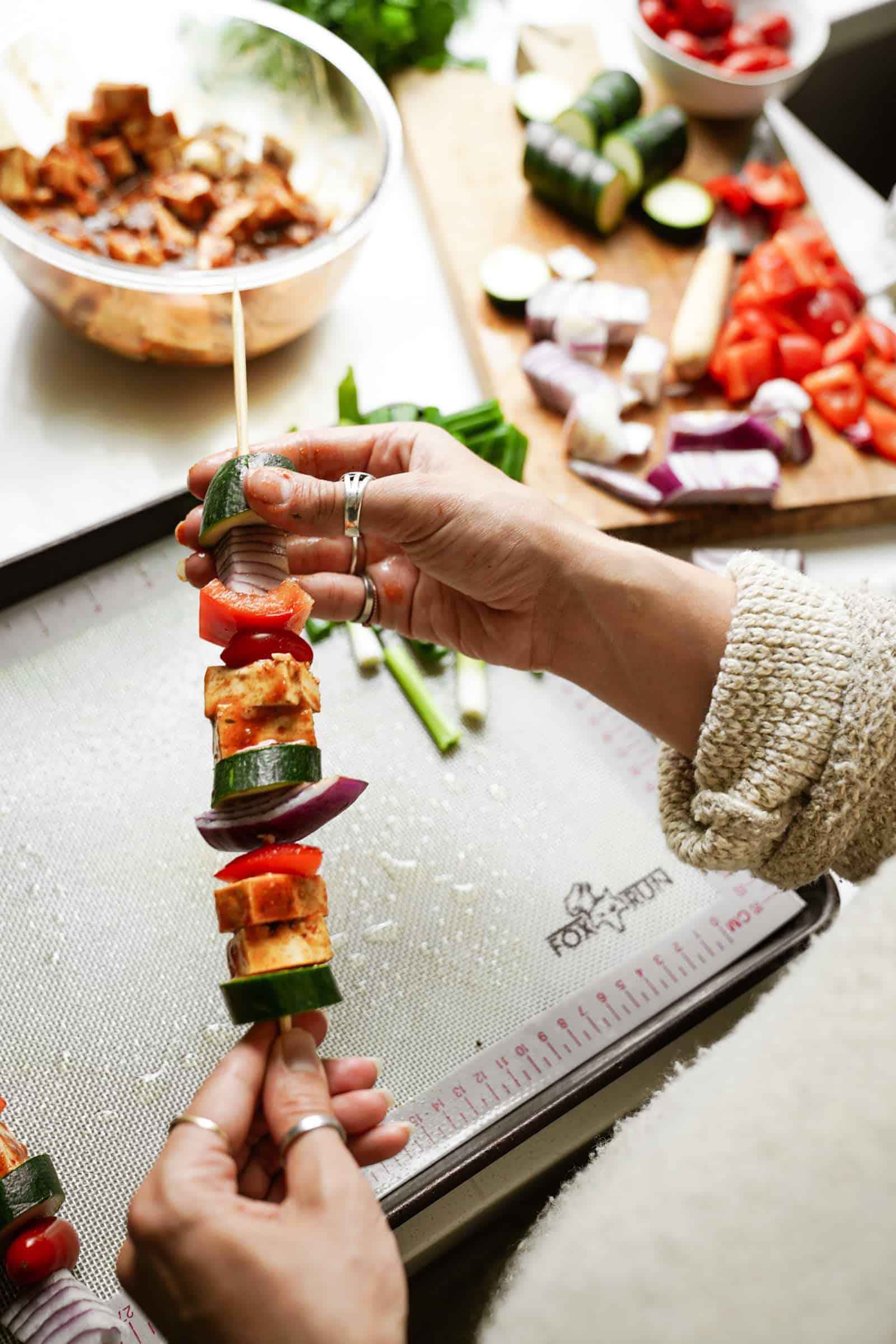 Veggies and tofu being put on skewers for Marinated Tofu and Vegetable Skewers