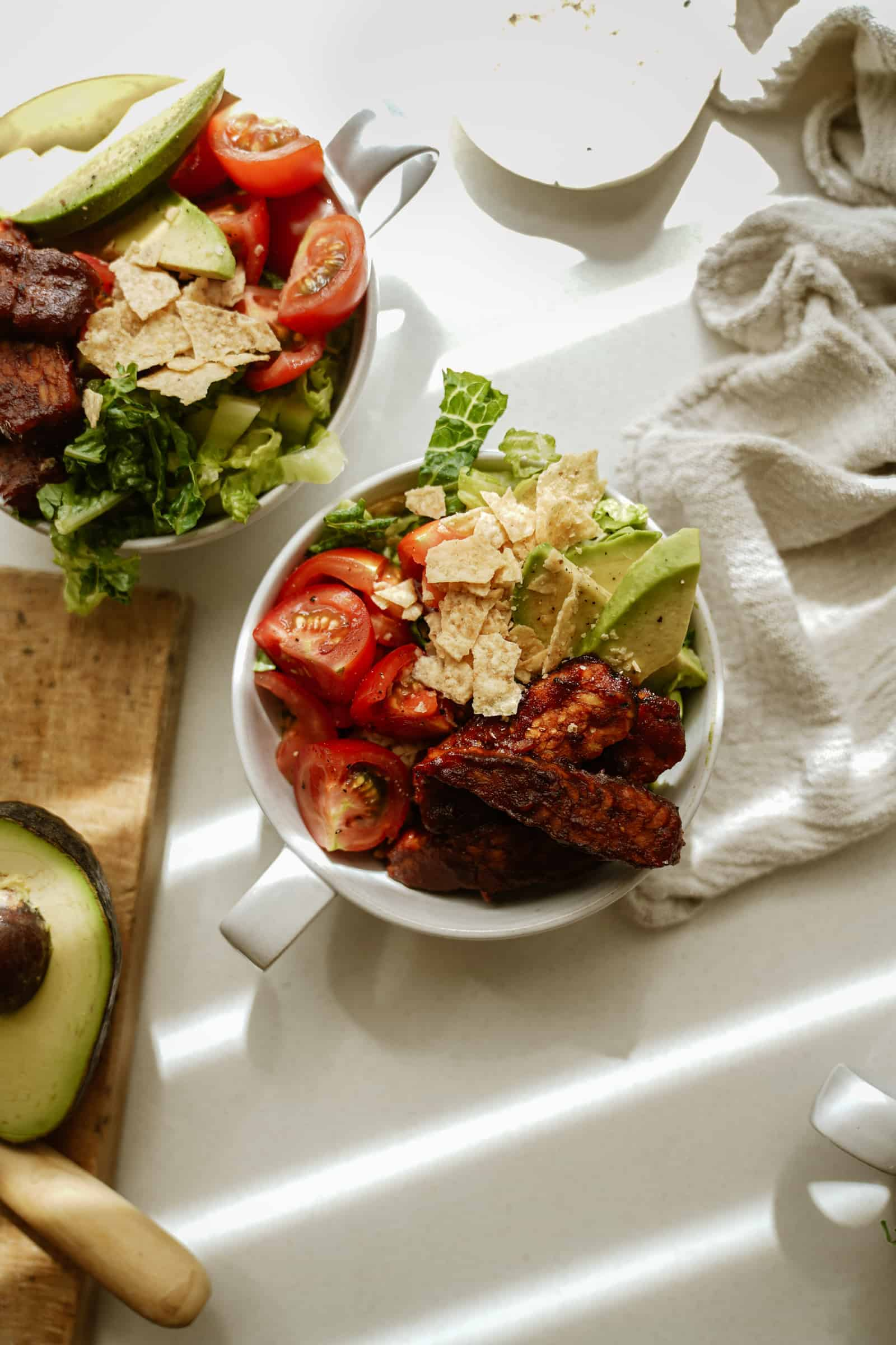 BBQ tempeh bowls on counter with fresh veggies