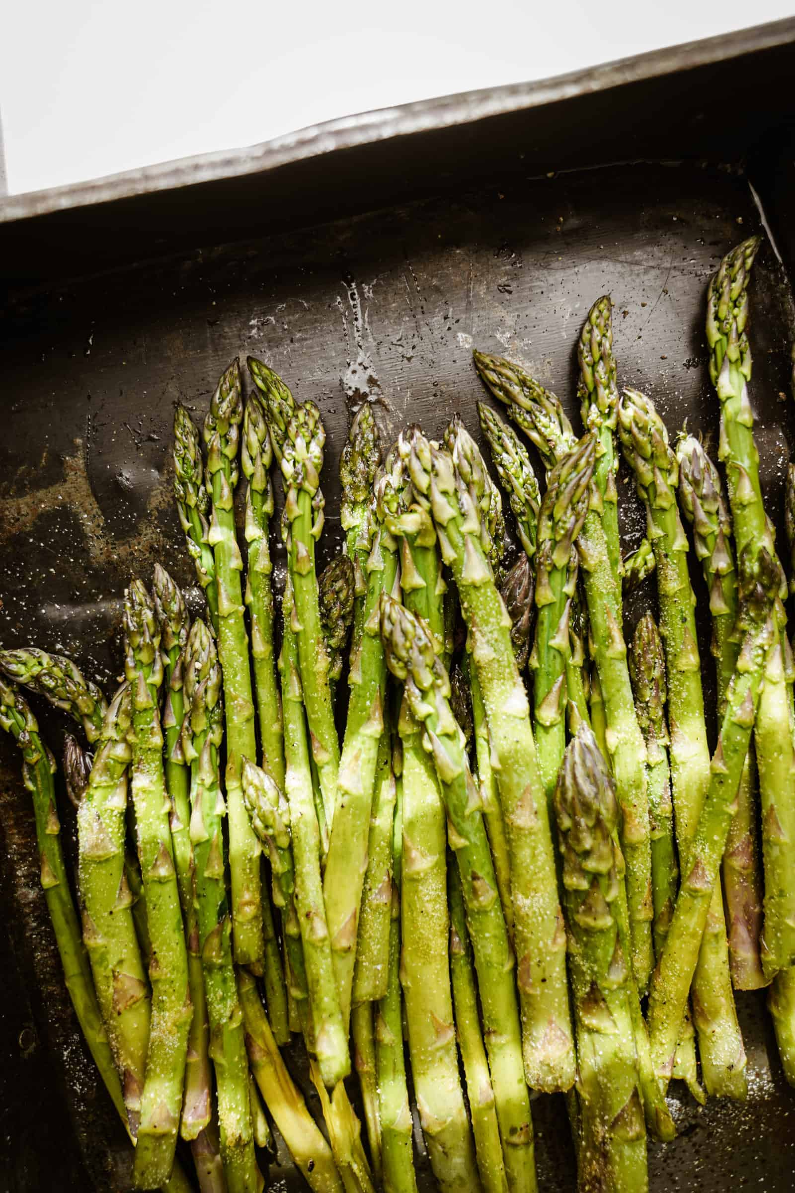 Raw asparagus on a baking tray