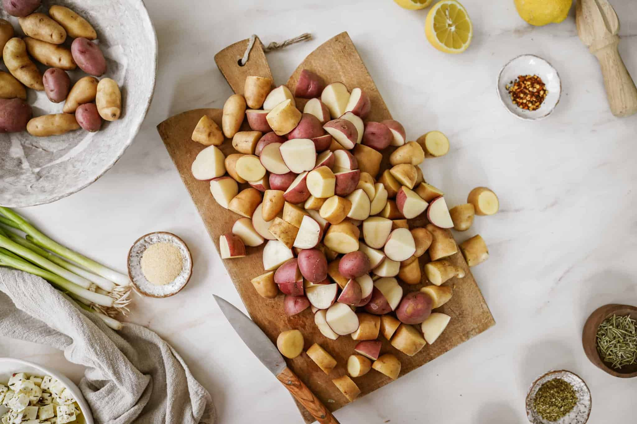Cut potatoes on cutting board for Greek potato salad