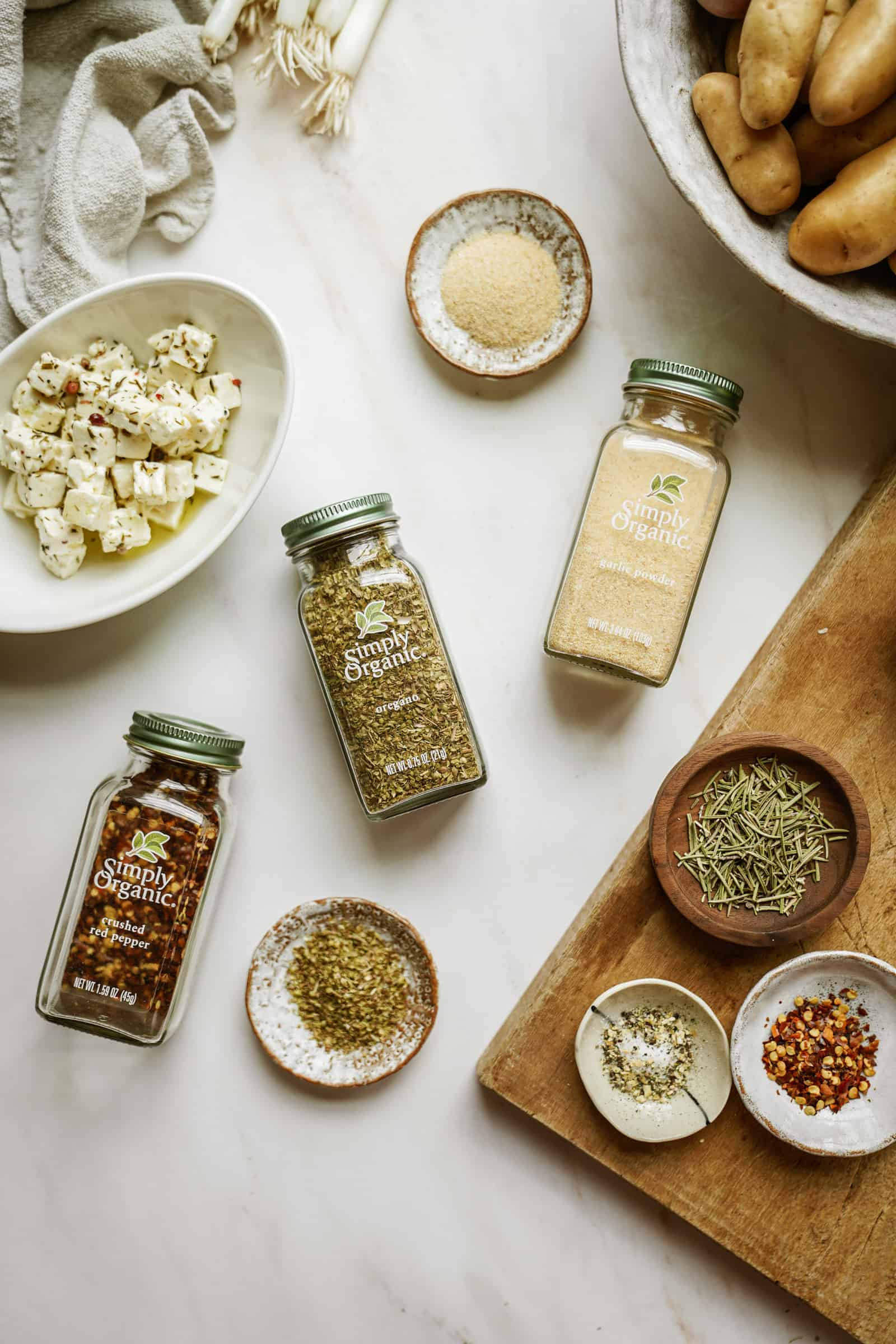 Simply Organic spices on a table surrounded by ingredients