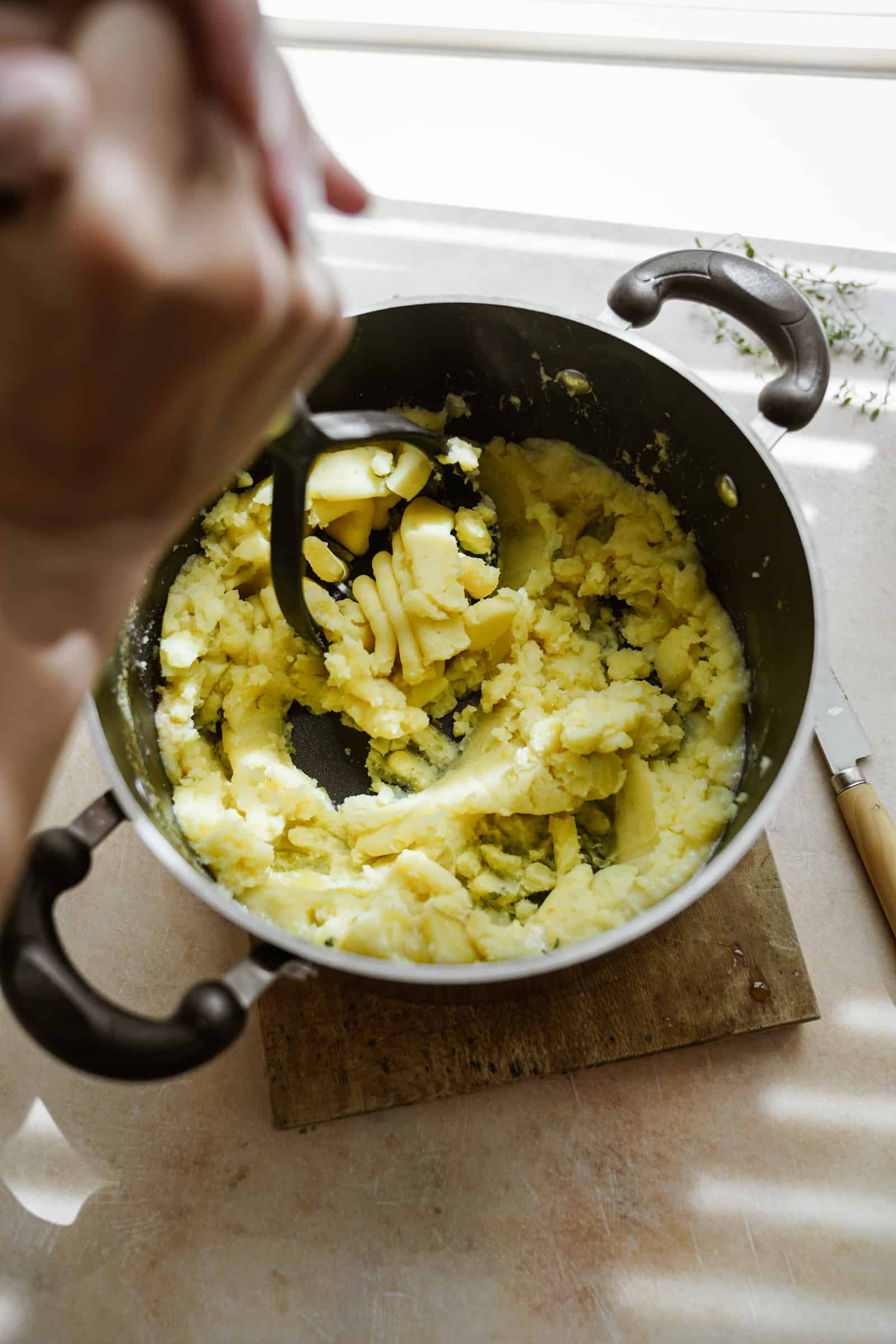 Mashing potatoes in pot