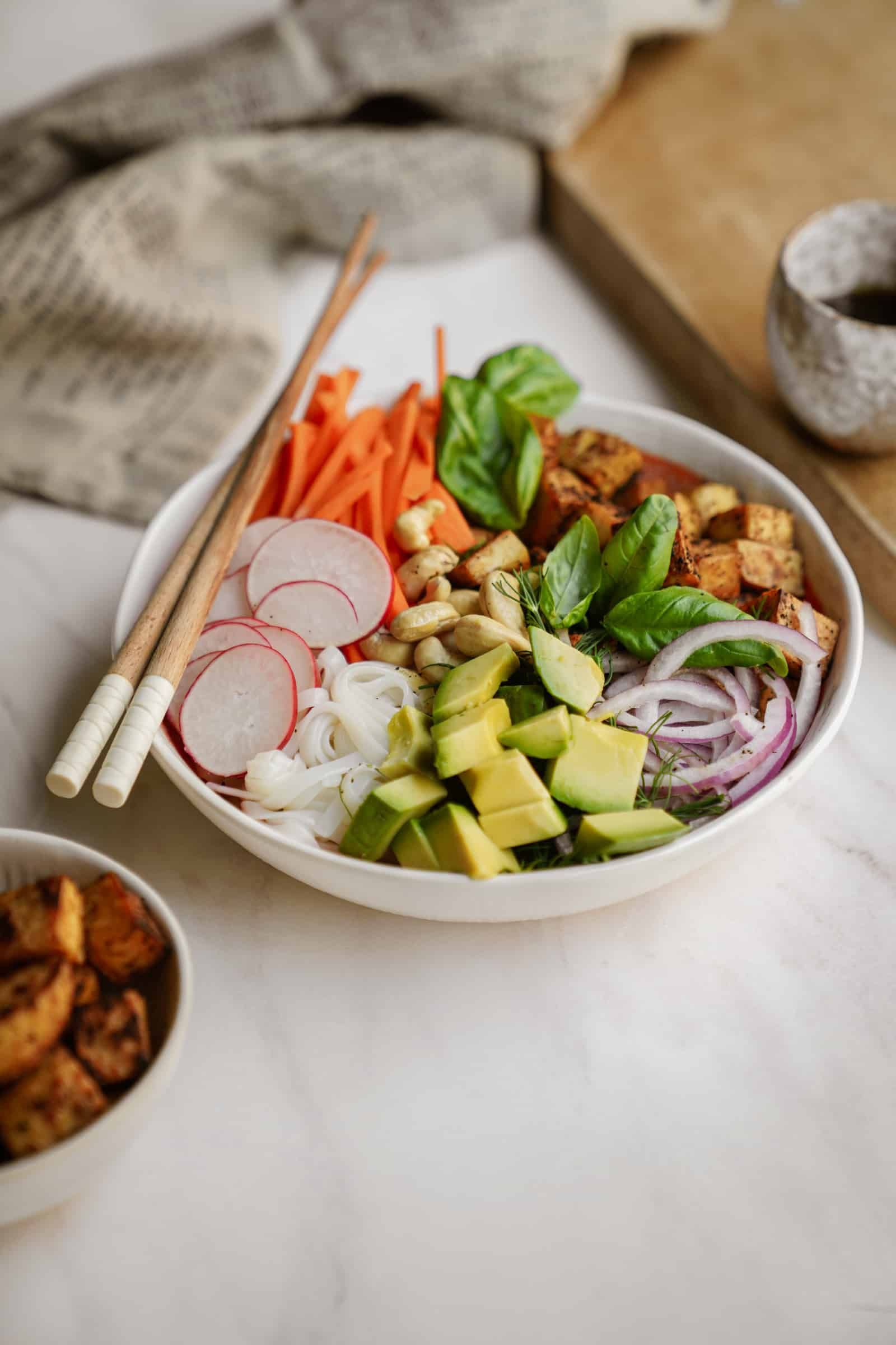 Crispy tofu noodle bowl on counter in white bowl with chopsticks
