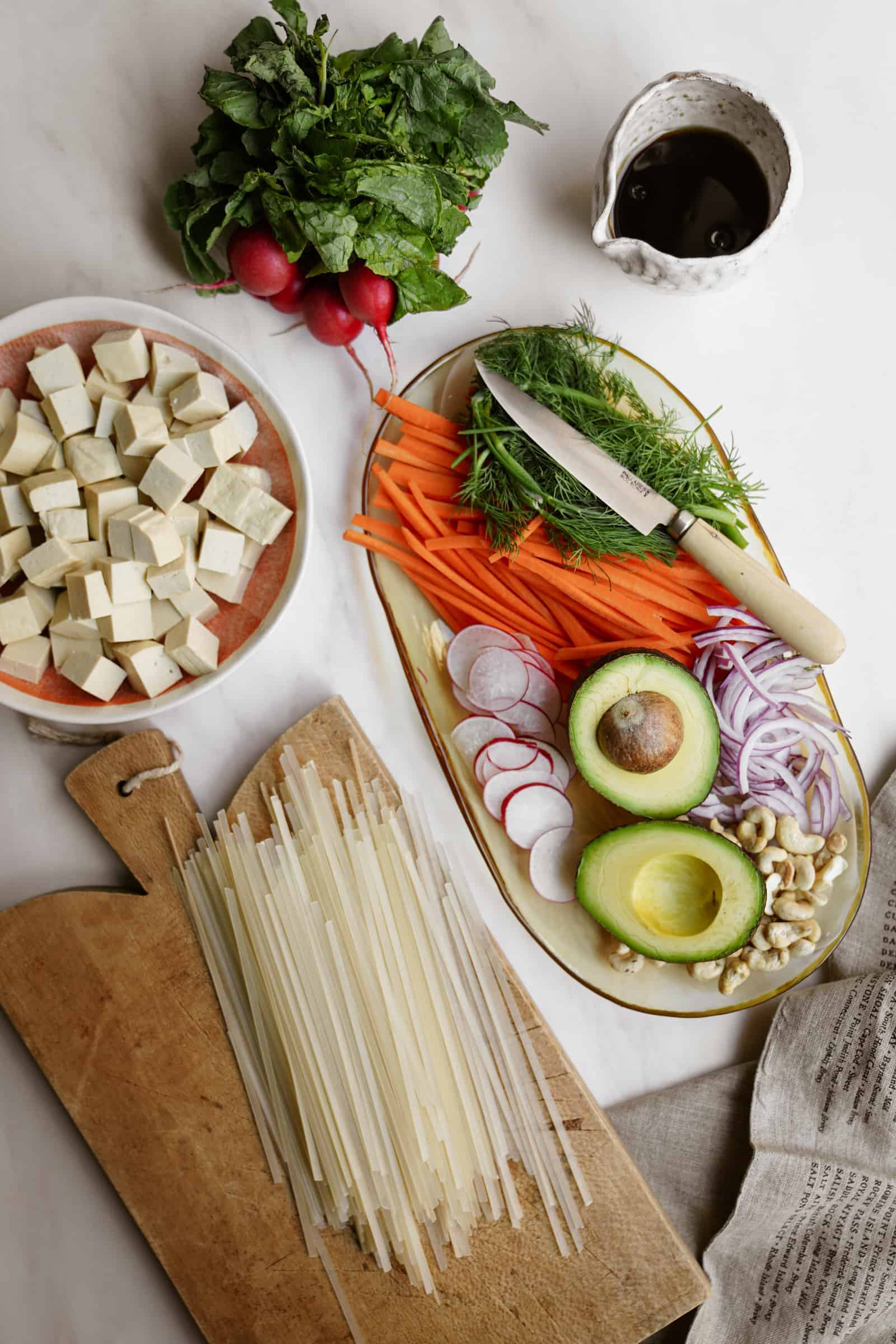 Ingredients for crispy tofu noodle bowl on countertop.