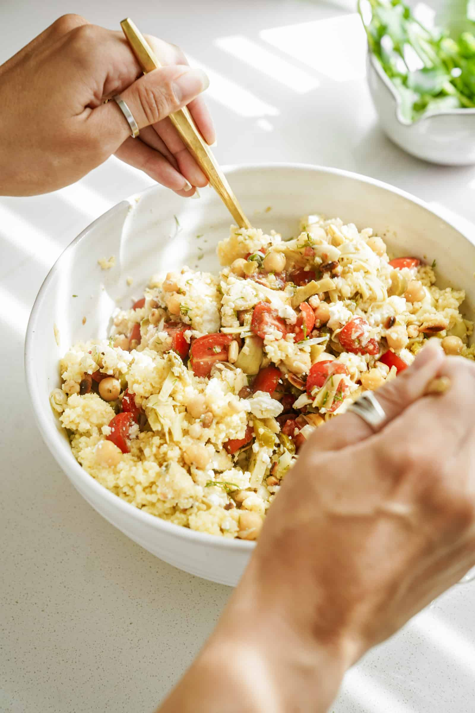 All ingredients being added to the Mediterranean Salad Recipe in a large serving bowl