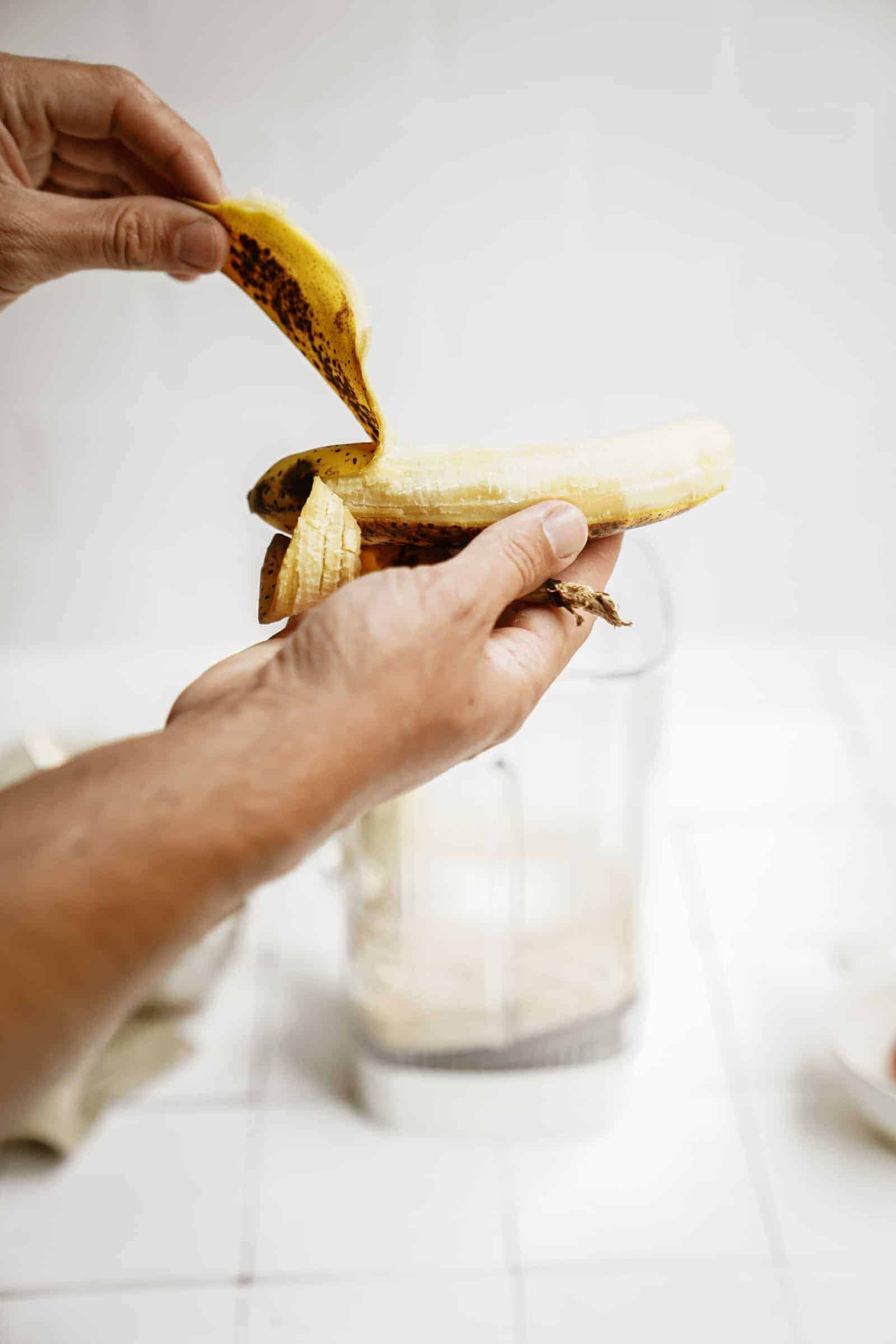 Banana being added into a blender for peanut butter banana pancakes