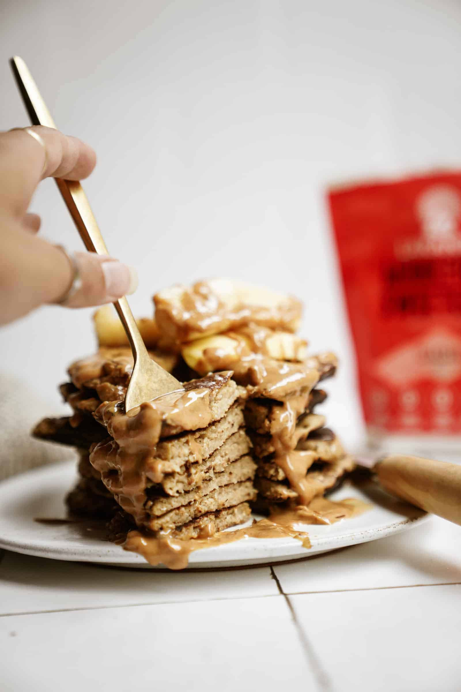 Stack of peanut butter banana pancakes with fork stabbing them