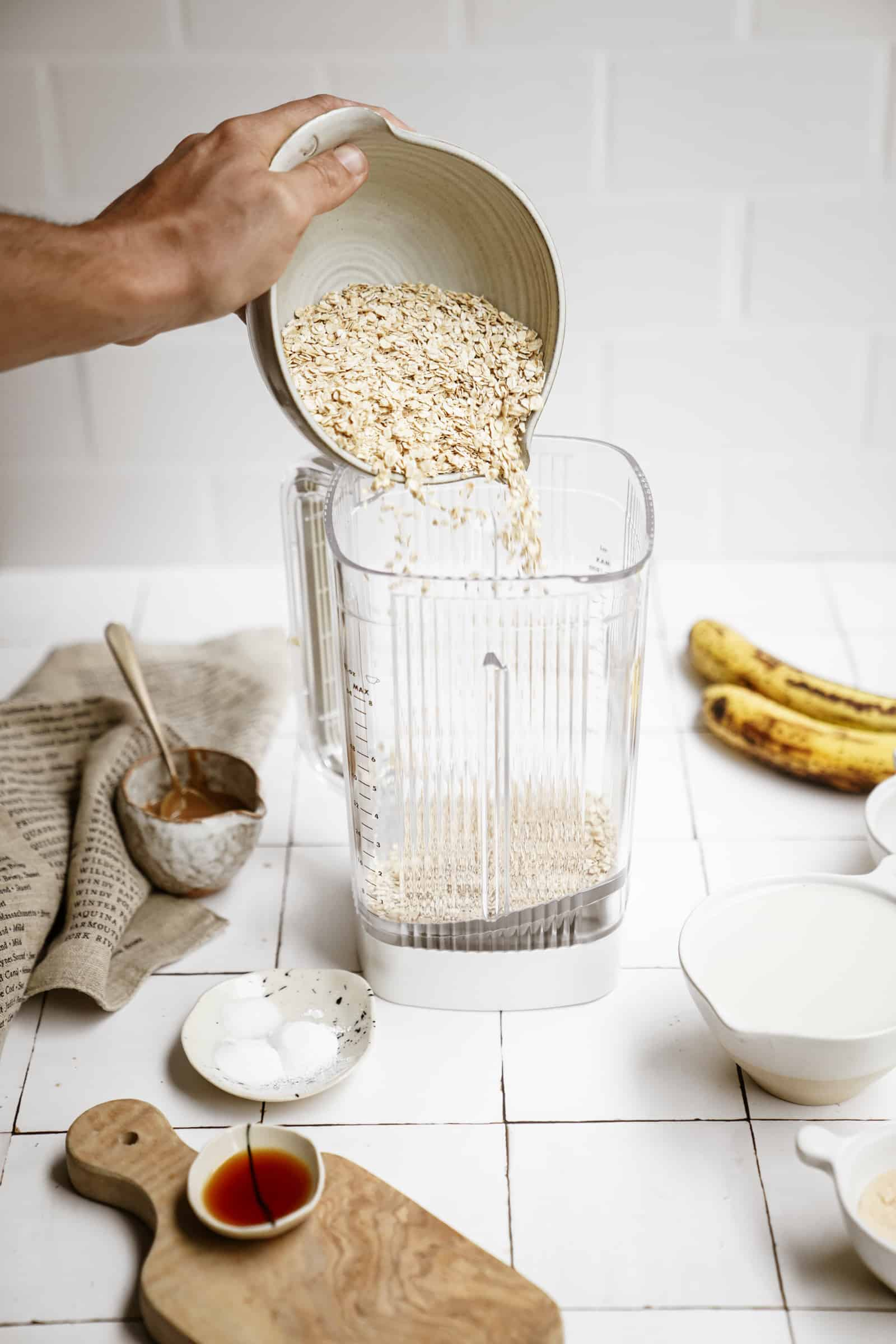 Oats being added into a blender for peanut butter banana pancakes