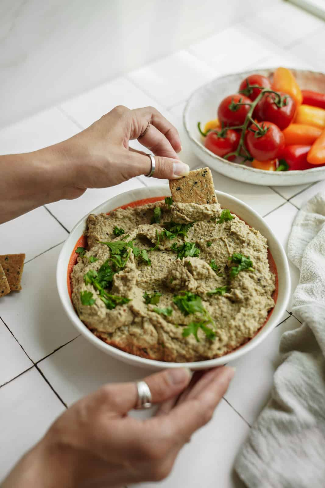 Big bowl of creamy eggplant dip with hand dipping cracker into it