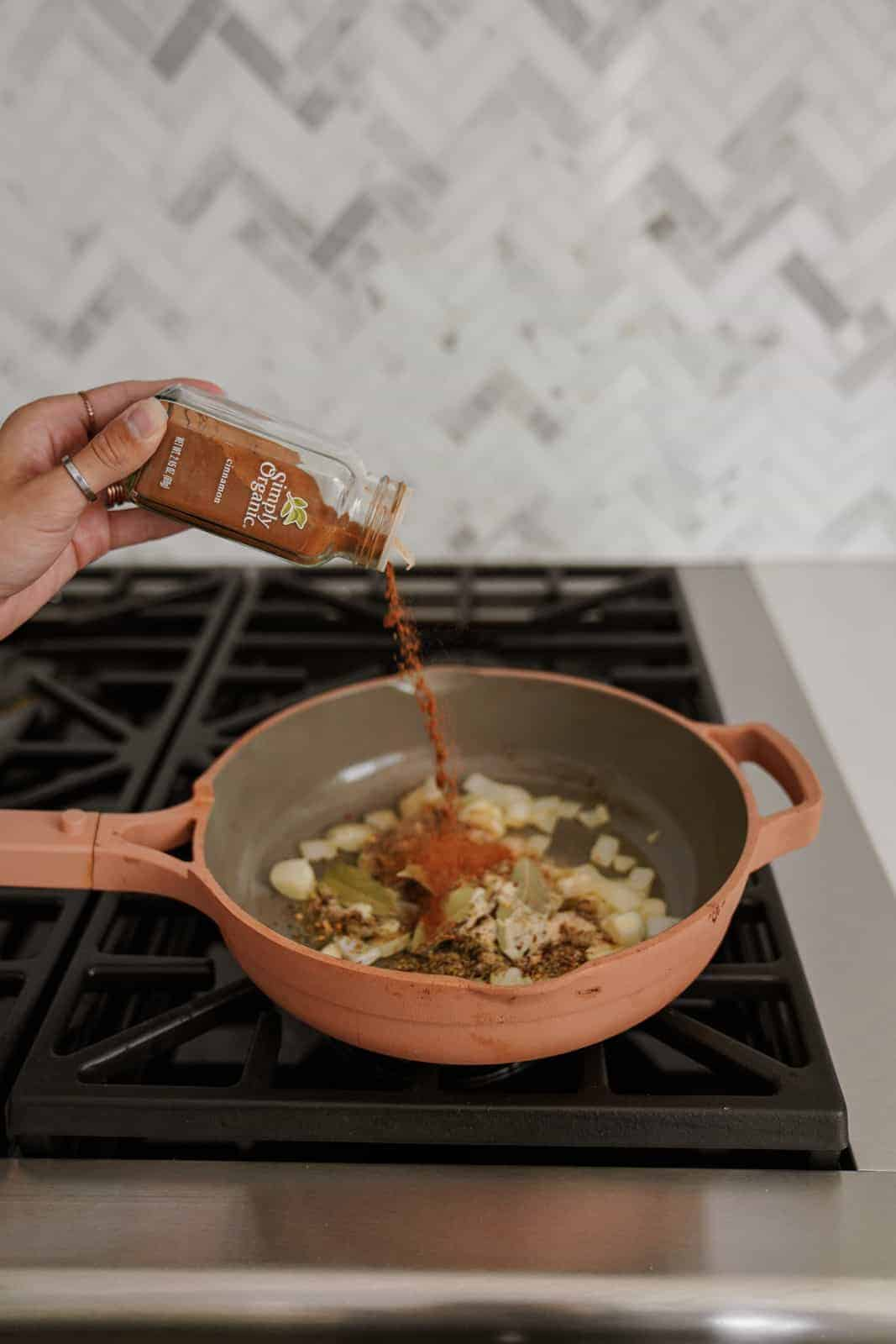 Adding spices into a pan on the stove