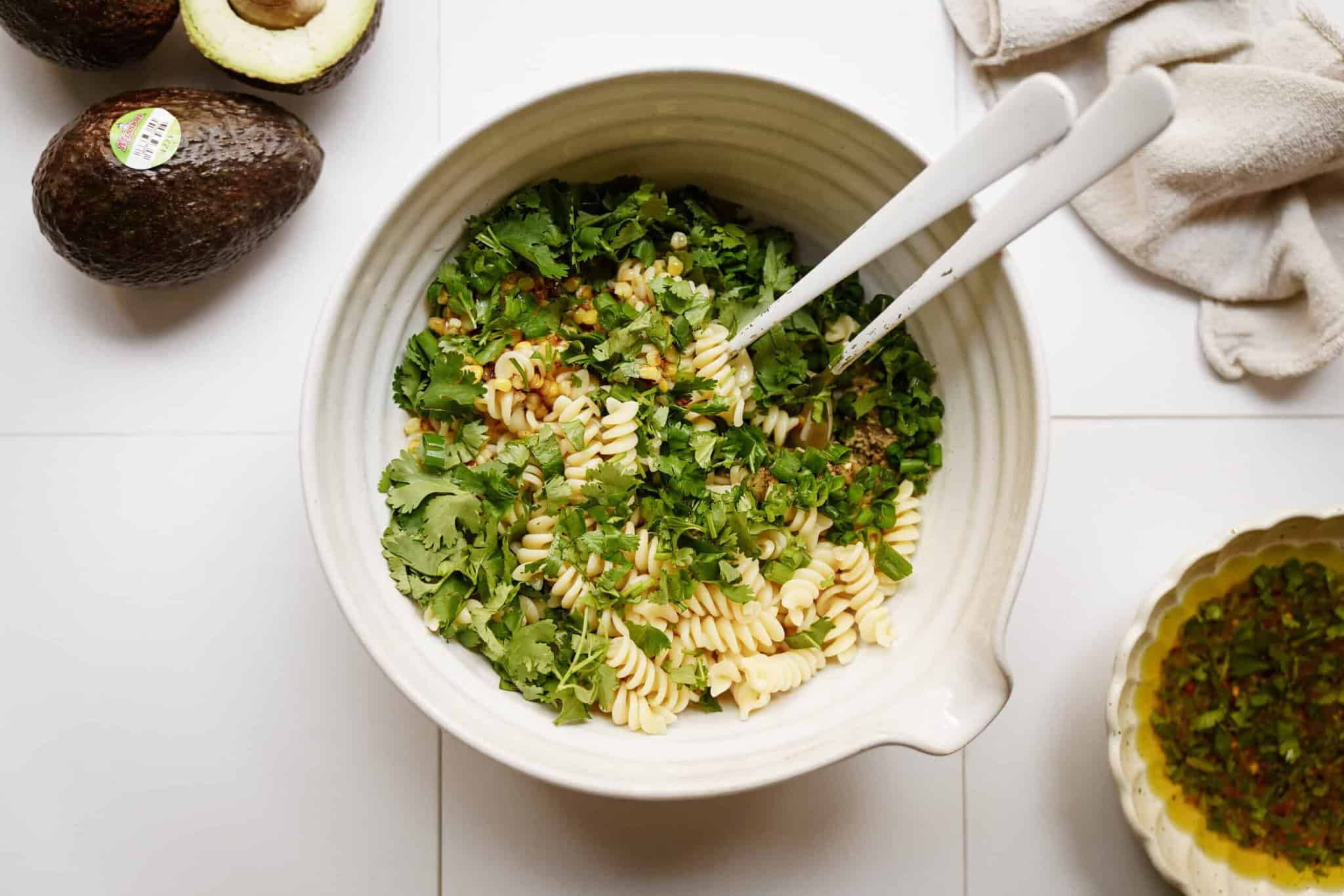Pasta with herbs in bowl for avocado pasta salad