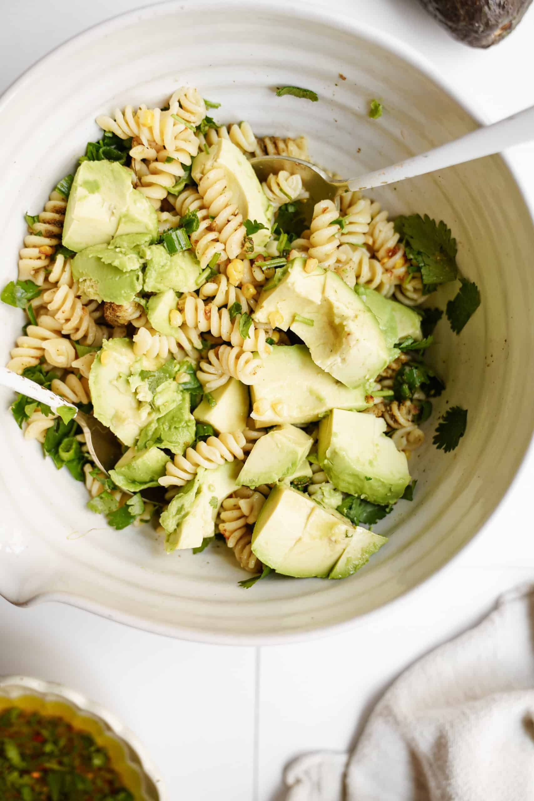 All ingredients for avocado pasta salad mixed in bowl