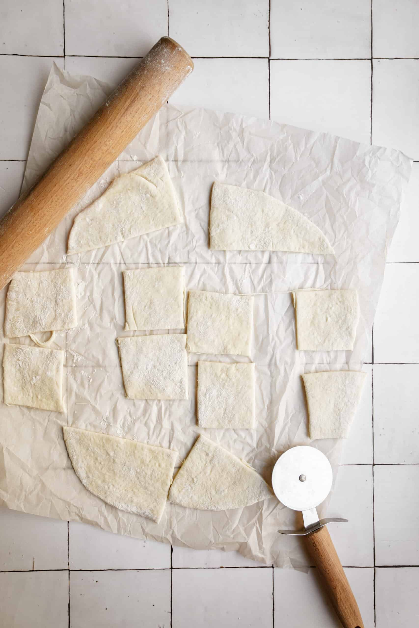 Pizza dough being rolled and cut on parchment