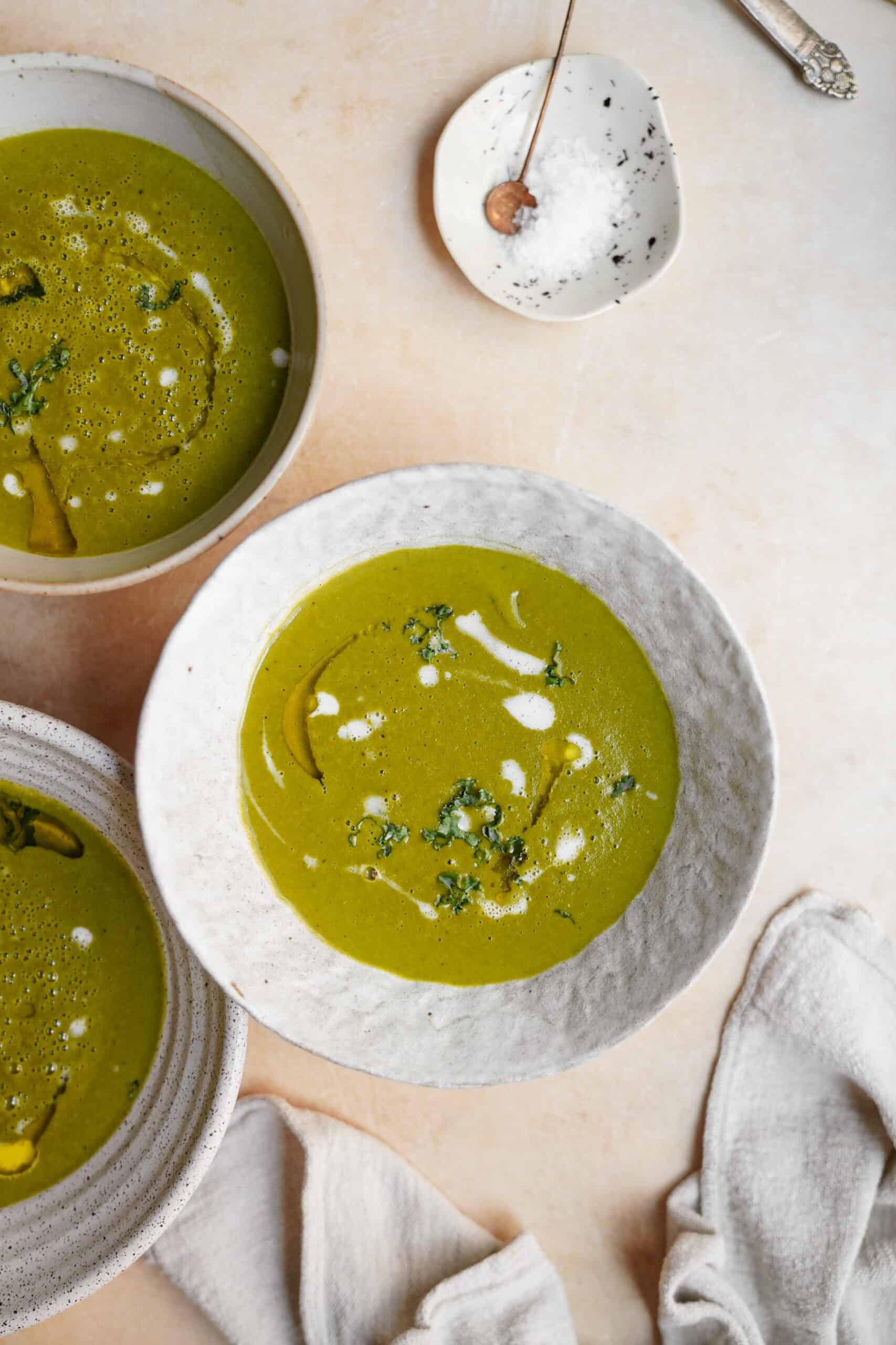 potato kale Soup in white bowls on countertop