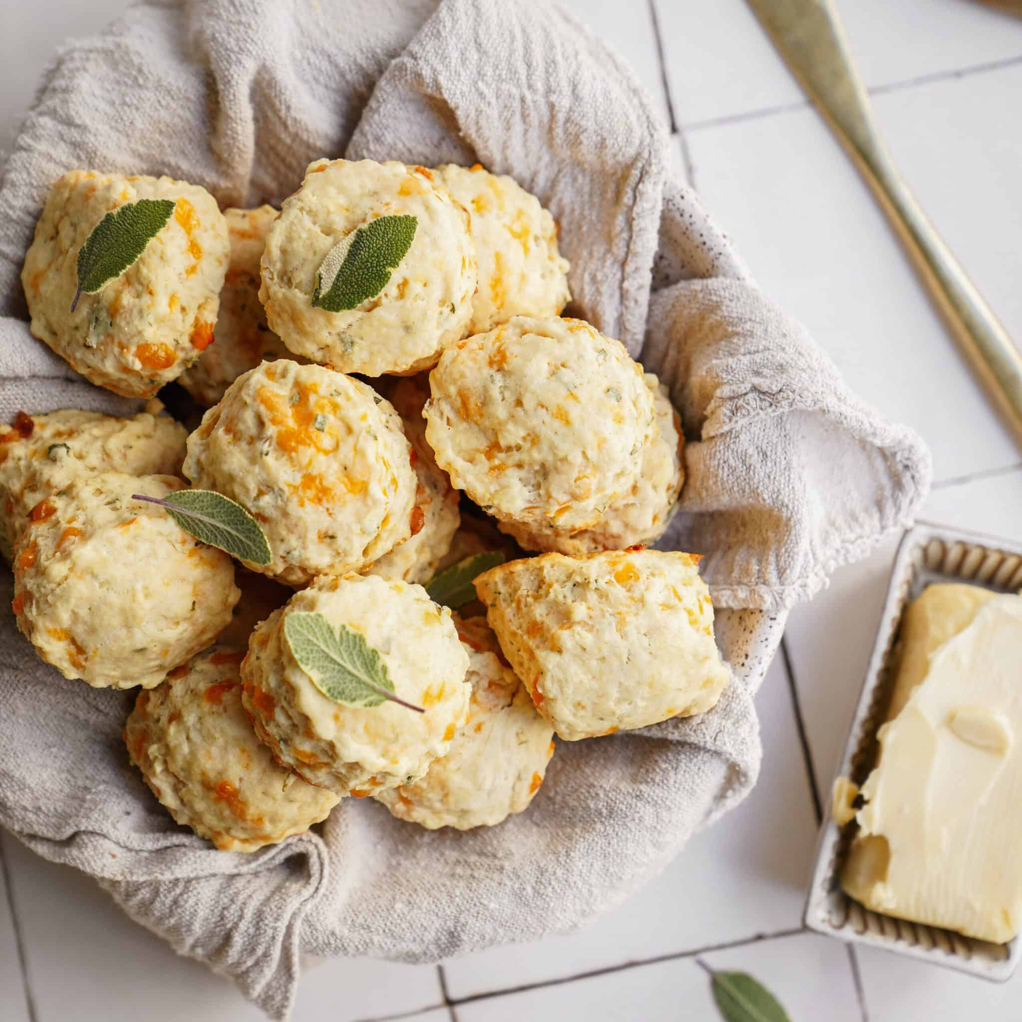 Cheddar biscuits in a basket with butter