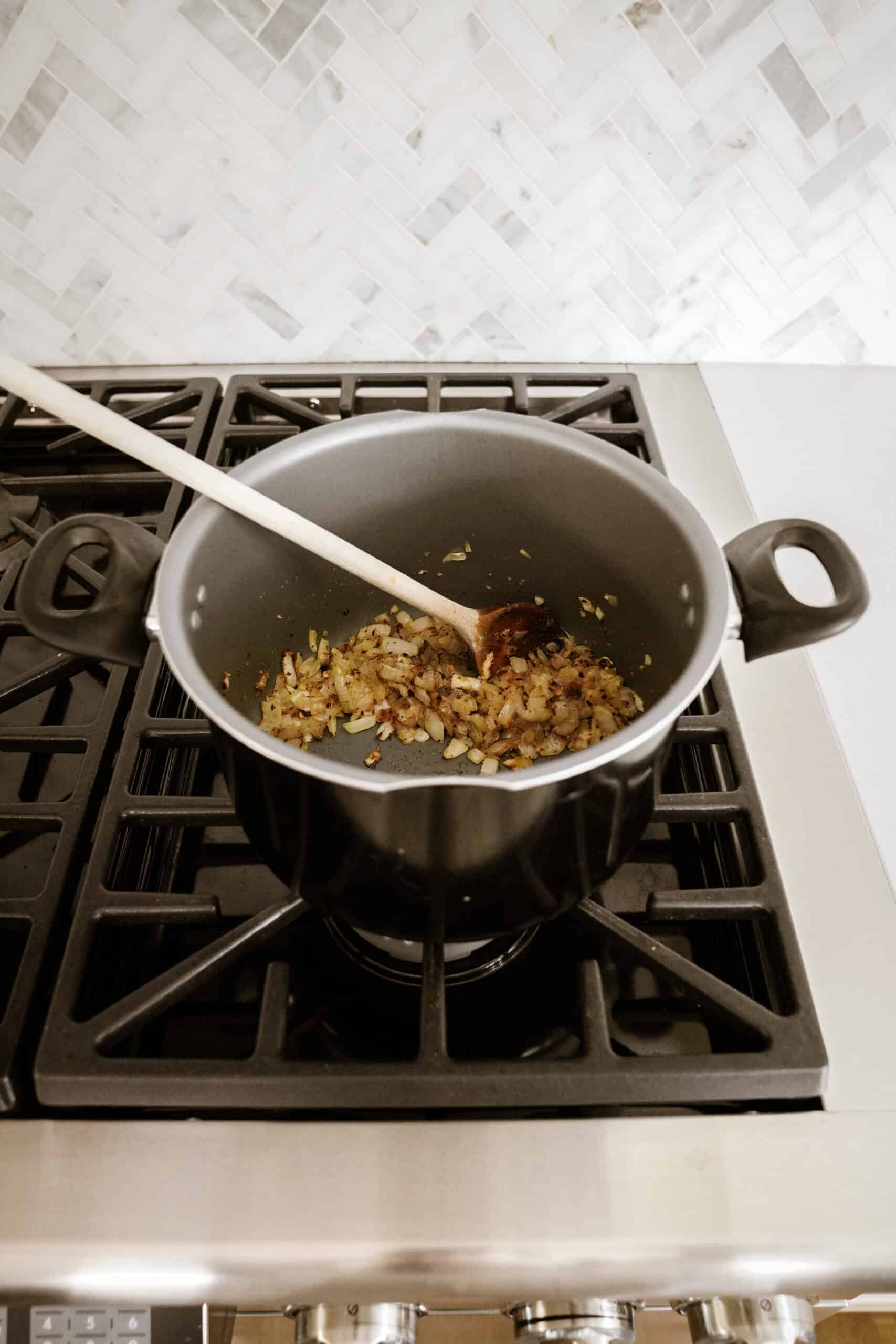 Onions in a pot on a stove with a wooden spoon