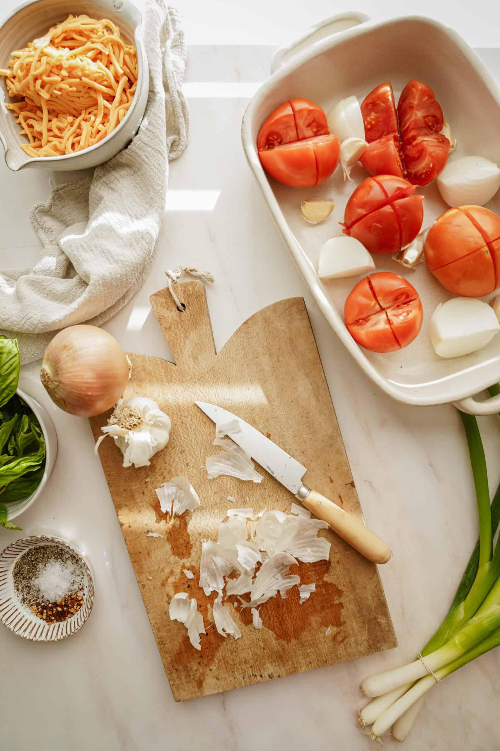 Prep for creamy tomato soup on a cutting board