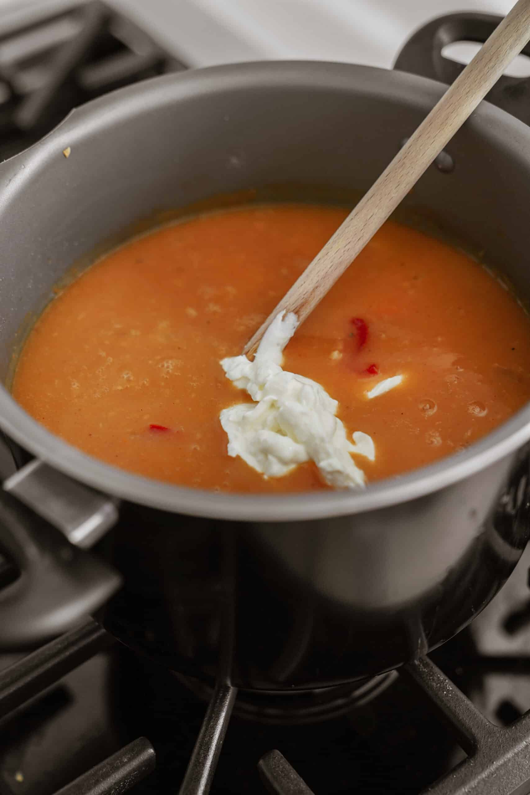 Cream being added into soup pot