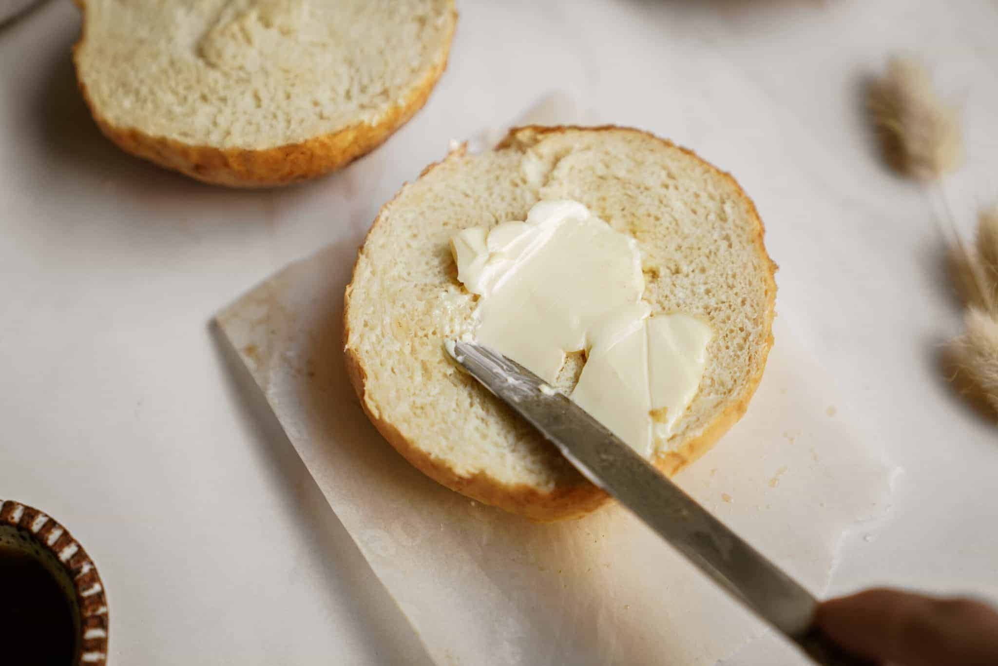 Butter being spread on dinner roll recipe