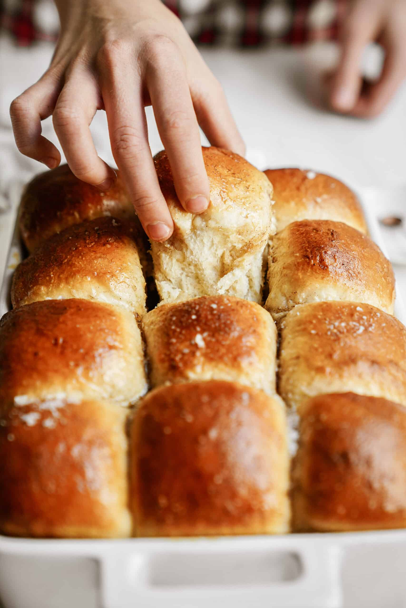 Hand taking dinner roll out of casserole dish