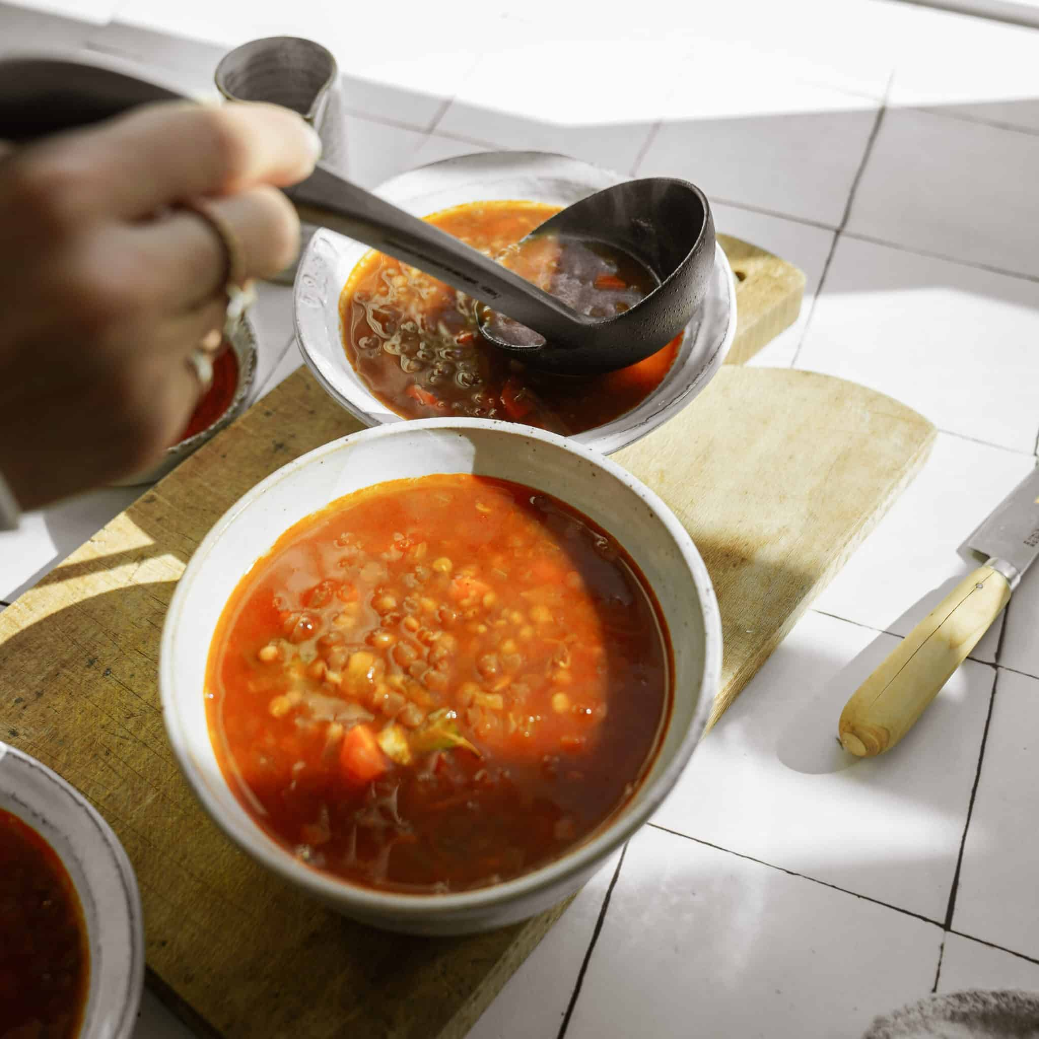 Greek lentil soup being scooped with a spoon